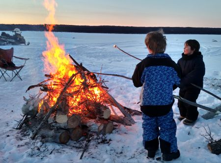 Huge winter fire and kids roasting marshmallows